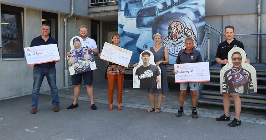 Mitarbeiter der Straubing Tigers und des EHCs halten Checks und Fanaufsteller in der Hand